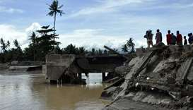 Residents looking at the Cabuyao Bridge, which collapsed after being hit by Tropical Storm Tembin, i