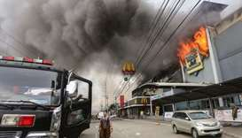 A firefighter standing in front of a burning shopping mall in Davao City on the southern Philippine