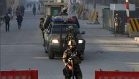 Afghan security forces keep watch at a check point close to the compound of Afghanistan's national i