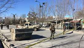 Afghan security forces stand guard near the site of multiple blasts in Kabul