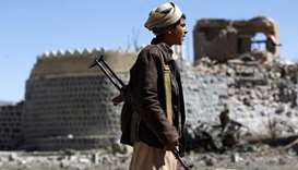 An armed Yemeni youth looks at the debris following an airstrike by the Saudi-led coalition on the g