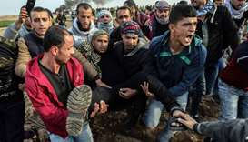 Palestinian protesters carry a wounded comrade during clash with Israeli forces near the Israel-Gaza