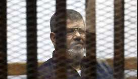 Deposed Egyptian President Mohamed Mursi listens to his verdict behind bars at a court on the outski