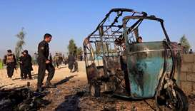 Afghan police officers inspect the site of a suicide attack on the outskirts of Jalalabad