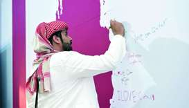 A visitor signs the pledge wall at Qatar Foundation's tent in Darb Al Saai.