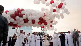 Balloons in Qatar's national colours and embossed with the famed Tamim Al Majd image are released at