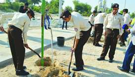 Students plant trees during the event at Education City