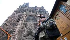 French soldiers stand guard at the Christmas market in front of the Cathedral as policemen conduct a