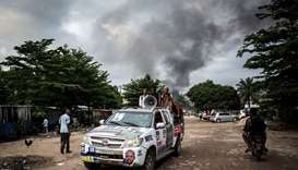 A campaign car is seen as smoke rises from a fire at the independent national electoral commission's