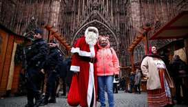 French police patrol outside the Strasbourg Cathedral as a man dressed as Father Christmas poses wit