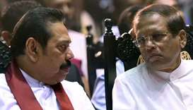 Sri Lanka's President Maithripala Sirisena (R) listens to former president and currently-appointed P