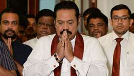 Sri Lanka's former president Mahinda Rajapakse gestures during a ceremony before signing a document