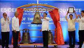 Philippine President Rodrigo Duterte (C) gestures as he rings one of the three Balangiga church bell