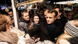 French President Emmanuel Macron (C) meets people as he visit the Christmas market in Strasbourg