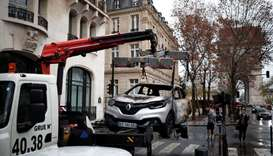 A vandalized car is removed the morning after clashes with protesters wearing yellow vests, a symbol