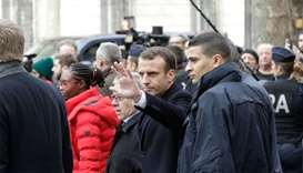 French President Emmanuel Macron (C, left) waves as he leaves the Cafe Belloy, near the Arc de Triom