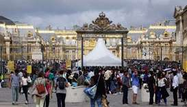 Tourists stand in queue at the entrance to the Chateau de Versailles (Versailles palace) in Versaill