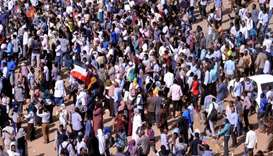 Sudanese demonstrators chant slogans as they march along the street during anti-government protests