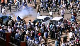 Sudanese demonstrators run from teargas lobbed to disperse them as they march along the street durin