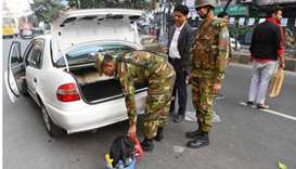 Bangladeshi army soldiers inspect a car at a roadblock ahead of December 30 general election, in Dha