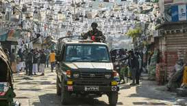 Bangladeshi army personnel drive a military vehicle through a street adorned with election posters n