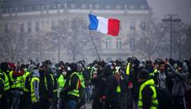 Demonstrators gather near the Arc de Triomphe as a French flag floats during a protest of Yellow ves
