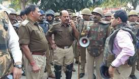 Policemen gather outside a police station following reports of mob violence at Chingravati village i
