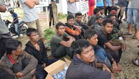 Suspected Rohingya people sit on the ground as they arrive in Idi Rayeuk, East Aceh