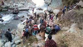 People gather at the accident scene where a bus fell into a gorge in the mountains of Poonch