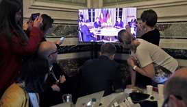 Media members watch a screen inside the press centre as Zelenskiy, Macron, Putin, and Merkel (not se