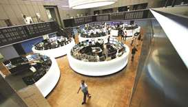 Traders work in front of the DAX board at the Frankfurt Stock Exchange. The DAX 30 closed 0.3% lower
