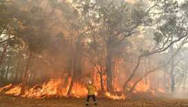A firefighter conducting back-burning measures to secure residential areas from encroaching bushfire