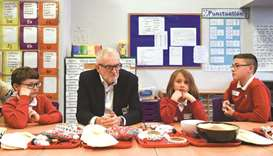 Opposition Labour party leader Jeremy Corbyn sits with school children during a campaign event at Sa