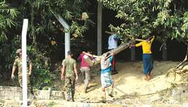 Labourers carry a concrete pillar as Bangladesh authorities prepare erecting pillars for barbed-wire