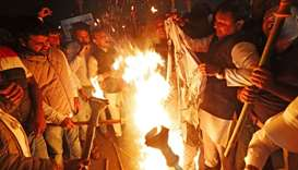 Members of the youth wing of India's main opposition Congress party burn a copy of Citizenship Amend
