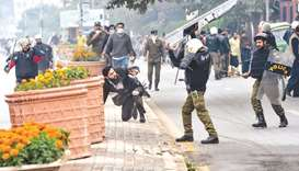 A policeman prepares to beat a lawyer (centre) following a clash between lawyers and doctors in Laho