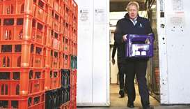 Prime Minister Boris Johnson carries a crate of milk to deliver to customers in Guiseley, Leeds, yes