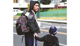 A migrant and his son deported from the US are seen outside the air force base upon their arrival in
