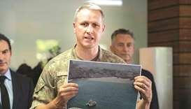 New Zealand Army Colonel Rian McKinstry holds a photo showing soldiers taking part in a mission to r