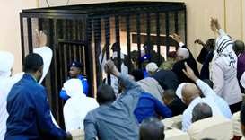 Sudanese former president Omar Hassan al-Bashir waves to supporters as he sits inside a cage during