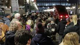 Commuters wait to take a train at Gare du Nord train station during a strike by all unions of French