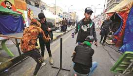 Iraqi volunteers search protesters at a makeshift checkpoint in Tahrir Square in the capital Baghdad