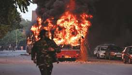 A man walks on a street as a bus is on fire following demonstration against the government's Citizen