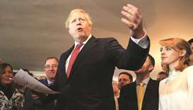 Johnson gestures while speaking with supporters on a visit to meet newly-elected Conservative party