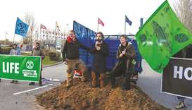 Activists from the climate action group Extinction Rebellion protest after dumping manure outside th