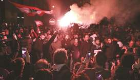 A Lebanese demonstrator uses a flare during an anti-government protest in the downtown area of the c