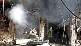 Smoke billows from a building following a reported bombardment by pro-Syrian government forces in th