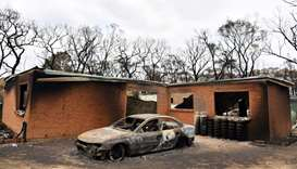 A house and car damaged by Saturday's catastrophic bushfires in the Southern Highlands village of Ba