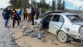 Libyans gather next to debris and damaged cars after a shell landed next to a vegetable store in the