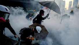 Anti-government protesters protect themselves with umbrellas against tear gas during a demonstration